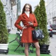 Stock Photo: Beautiful young woman in red coat on the street