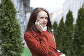 Young woman calling by phone on the street — Stock Photo
