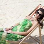 Young beautiful woman relaxing lying on a sun lounger — Stock Photo #26840823