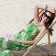 Young beautiful woman relaxing lying on a sun lounger — Stock Photo #26840831