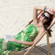Young beautiful woman relaxing lying on a sun lounger — Stock Photo #26840839