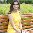 Brunette sitting on a bench in a summer park — Stock Photo