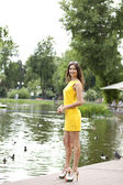 Attractive young woman in yellow dress — Stock Photo