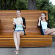 Three young women on a summer park bench — Stock Photo