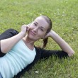 Young woman lying on the grass with phone in hand — Stock Photo