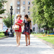 Two young women walking in the summer city — 图库照片