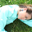 Portrait of young woman lying on a green lawn — Stock Photo #28028123
