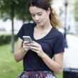 Young woman reading a message on the phone — Stock Photo