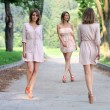Beautiful young women walking on the summer park — Stock Photo