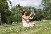 Portret młodej kobiety siedzącej na zielony trawnik — Zdjęcie stockowe