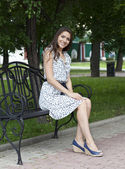 Beautiful young woman sits on a bench — Stok fotoğraf