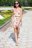 Beautiful young woman walking on the summer park — Stock Photo