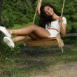 Happy woman riding on a swing in the park — Stock Photo
