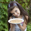 Little girl holding a plate with a white currants — Stock Photo
