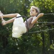 Happy little girl riding on a swing in the park — Stock Photo