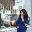 Young woman looking at shop window boutique — Stock Photo