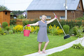 Pensioner in the country cottage with a bucket and mop — Stock Photo