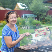 Mature woman Cooking On A Barbeque in the garden — Stock Photo