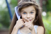 Little girl holding a comb in his hand — Stock Photo