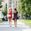 Two young women walking in the summer city — Stock Photo