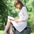 Blonde girl reading a book in the park  — Photo