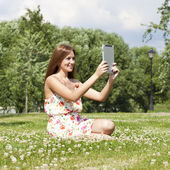 Portrait of young woman sitting on a green lawn — Stock Photo
