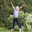 Happy little girl jumping in summer day — Stock Photo