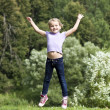 Stock Photo: Happy little girl jumping in summer day