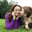 Mother and son lying on the green grass in the park — Stock Photo