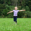 Little girl running on the meadow in summer day — Stock Photo