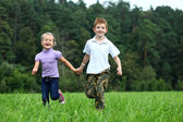 Bambini che corrono sul prato verde del parco — Foto Stock