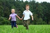 Děti běží na zelené trávě v parku — Stock fotografie