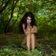 Stock Photo: Mysterious naked girl sitting in a dark forest