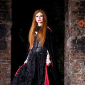 Terrible vampire woman in a red cloak — Stock Photo