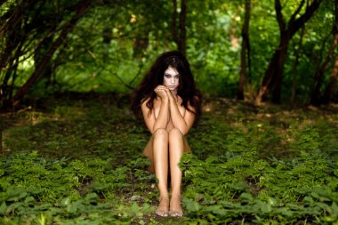 Mysterious naked girl sitting in a dark forest