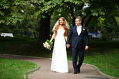 Happy bride and groom walking in the summer park — Stock Photo