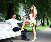 Young bride and groom in the summer park — Stock Photo