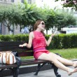Beautiful young woman sits on a bench  — Stock Photo