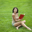 Young beautiful young woman reading a book outdoor  — Stock Photo