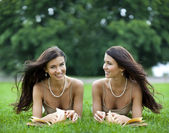 Twins young women reading a book outdoor — Stok fotoğraf