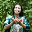 Happy woman holding apples, against green of summer park. — Stock Photo