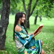 Blonde girl reading a book in the park  — Stock Photo