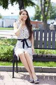 Brunette assise sur un banc dans un parc d'été — Photo
