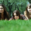 Three young women lying on a green lawn — Stock Photo
