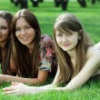 Three young women lying on a green lawn — Stock Photo #34401293
