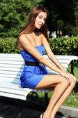 Bruneta sedí na lavičce — Stock fotografie
