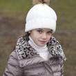 Little girl in a white knitted hat autumn — Stock Photo