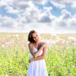 Young woman walks in summer field — Stock Photo