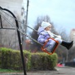 Little girl riding on a swing in the park — Stock Photo