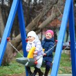 Little girls riding on a swing in the park — Stock Photo